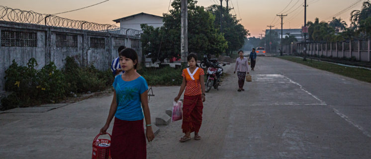 Garment factory workers walk to Myanmar Century Garment in the early morning before work.