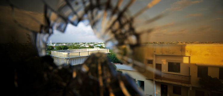 A view of the skyline beyond the northern suburbs of Mogadishu is seen through a bullet hole in the window of a hotel in the Yaaqshiid District of Mogadishu, where African Union Mission in Somalia (AMISOM) forces have pushed Al Shabaab militants beyond the city's northern fringes to the outskirts of the Somalia seaside.