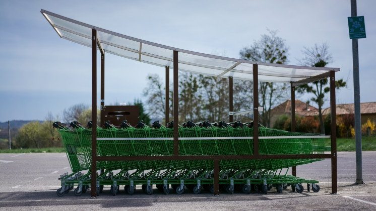 Green shopping carts in front of a mall in Forcalquier, Haute Provence, France
