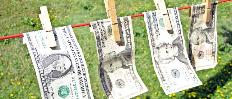 Laundering Dollar Bills  4 dollar bills on the washing line with a green pasture in the background