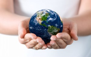 Image of a globe carried by two hands symbolising SOMO Services