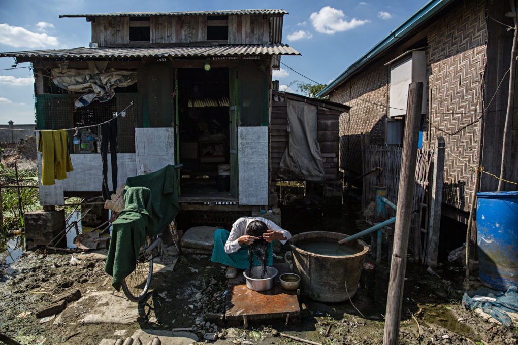 A woman washes her hair outside of her home in a squatter village where many garment factory workers live.