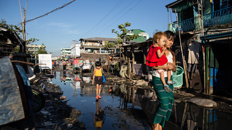 A woman and children walk down the flooded streets of Yangon's Hlaing Tharyar industrial Zone, an area that houses many garment factory workers.