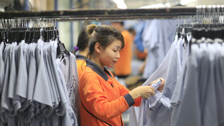 A young worker checks final products at a garment factory.